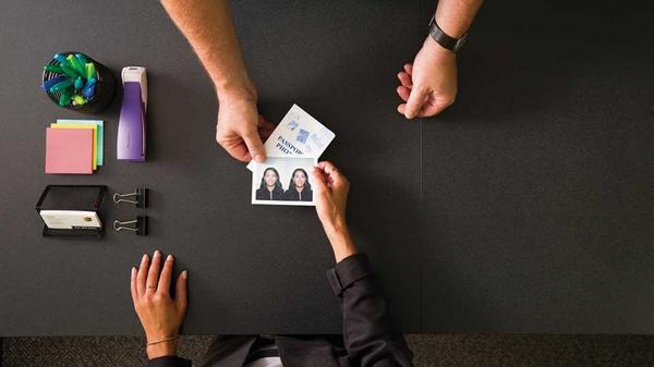 Handing a passport photo across a desk