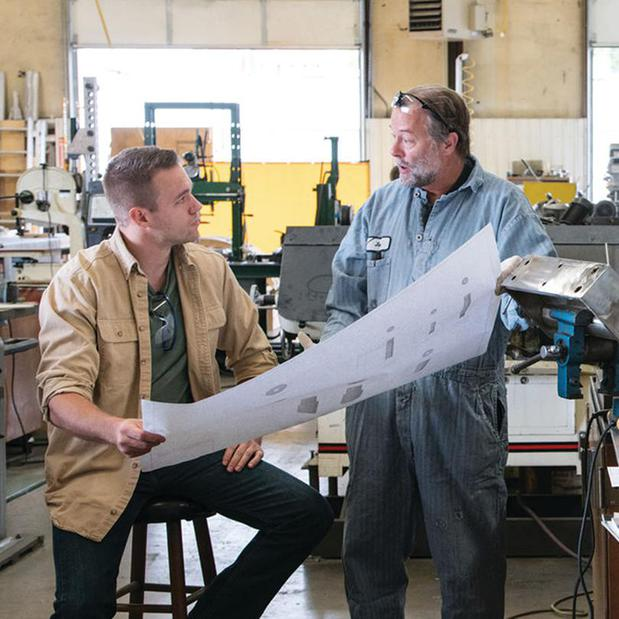 two men in a workshop looking at a blueprint and discussing