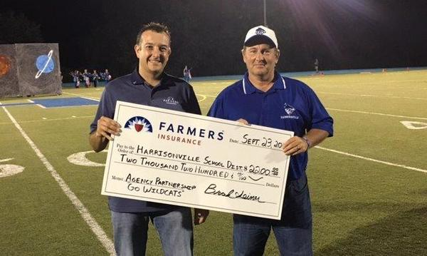 Farmers agent presenting a giant check to Harrisonville High School Superintendent Frank Dahman in 2016