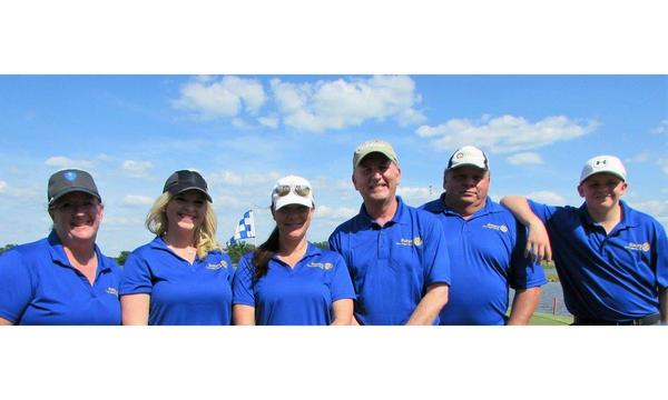 A photo of the team wearing matching Farmers polo shirts standing outside on a sunny day