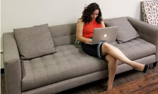 Sitting on the couch with an Apple notebook on her lap.