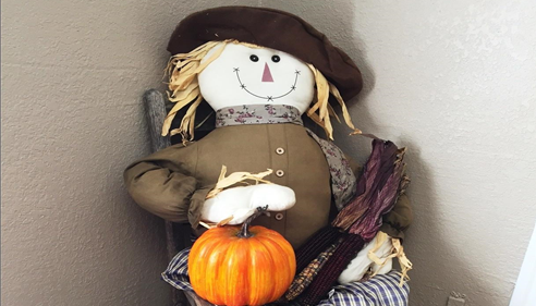 A scarecrow decoration holding a pumpkin.