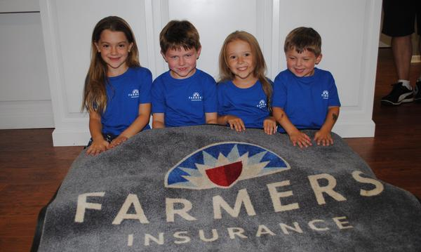 Agent's grandchildren under a Farmers Insurance blanket