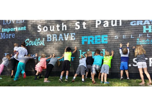 "children pose against a wall with various positive adjectives written on it, as well as ""South Saint Paul"""