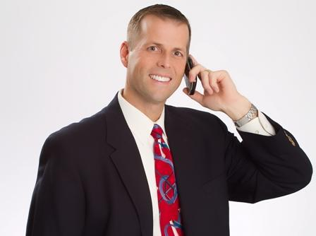 Photo of agent in suit holding his phone to his ear.