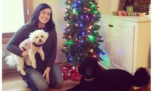 Agent holding a small white dog, kneeling next to a black dog and a christmas tree