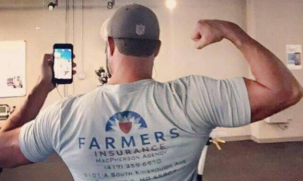 man wearing a farmers shirt, flexing his muscles.