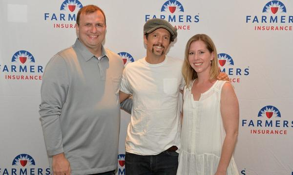 A couple posing with international superstar Jason Mraz, in front of a Farmers logo wall.