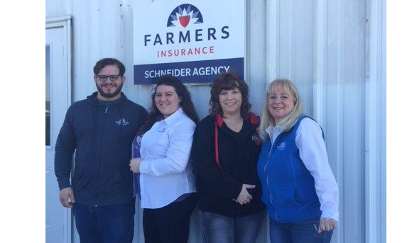 Agent Schneider and Agency Team In front of Farmers sign