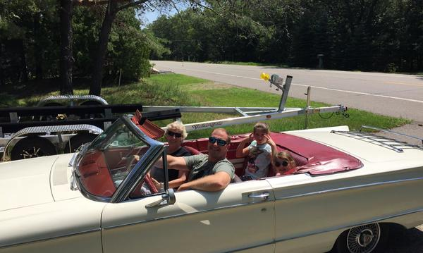 family smiling in white classic car