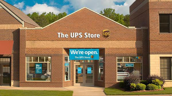 Exterior of The UPS Store with We're Open sign in front