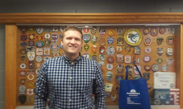 Man standing in front of a wall of badges.