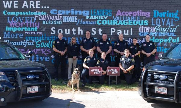 Nine police officers, a dog and a woman in front of wall for South Saint Paul.