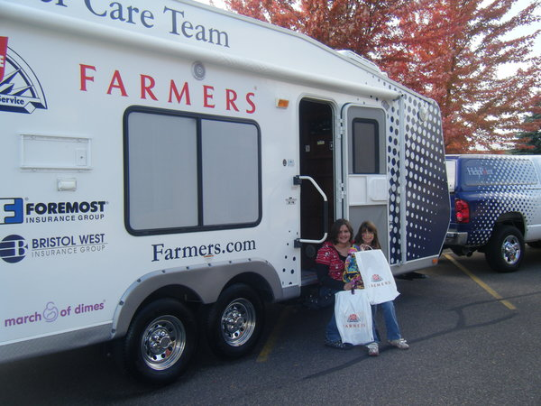 Two young girls standing in front of the mobile Farmers Customer Care Team center.