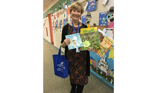 Teacher from Mackeben Elementary School holding donated books