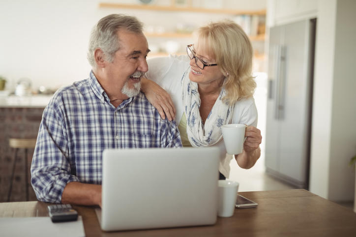 older couple smiling at one another while having coffee in front of a laptop