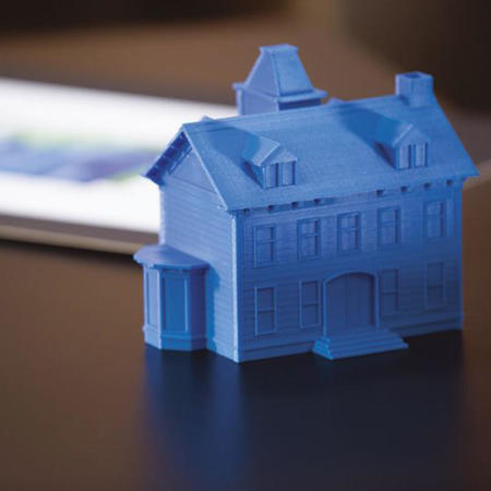 3D printed blue house on desk next to blurred document