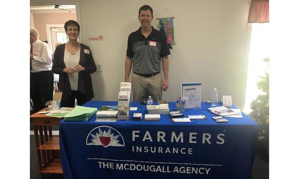 Agent William McDougall and a female staff member standing behind a blue Farmers Insurance The McDougall Agency table.