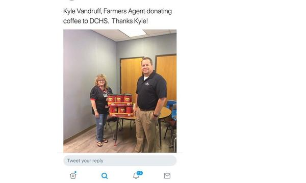 Farmers agent posing with teacher and coffee that he donated