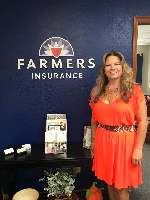 Woman posing with Farmers Insurance wall banner