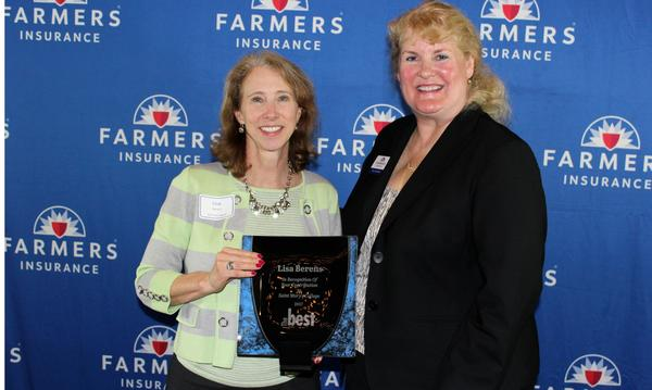 Two women posing with Farmers Insurance awards