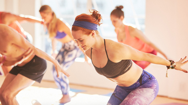 A woman stretches in a CorePower Yoga session with several women in the background.