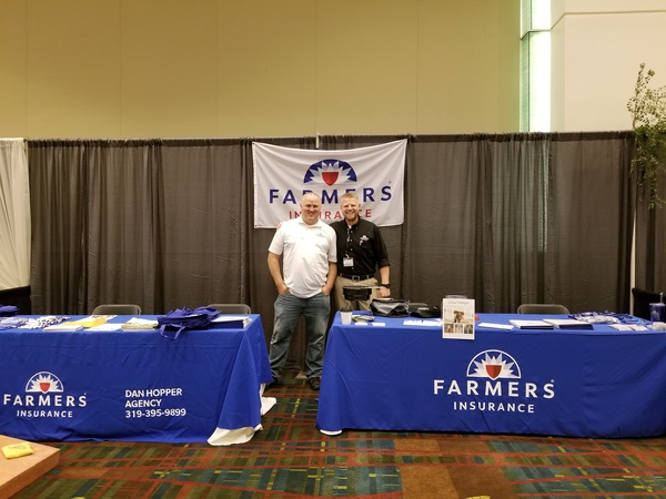 Agent - Nicholas Thies and Agent - Dan Hopper posing in front of Farmers booths.
