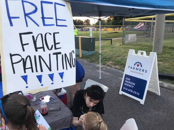 child getting face painted by adult, free face painting sign