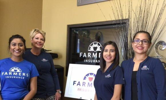 Four women in Farmers Insurance shirts standing in front of a Farmers Insurance sign.