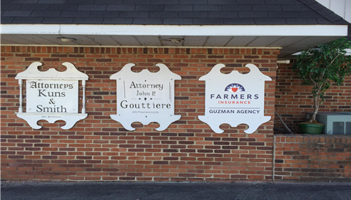 A photo of a Farmers Insurance Agency sign next to two other signs.