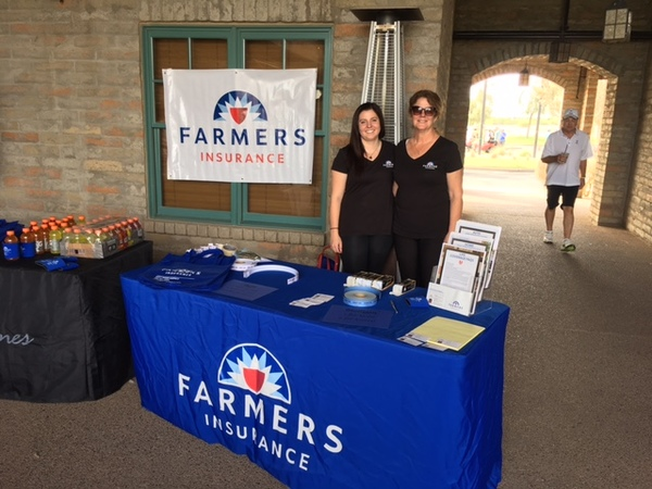 Agent Lucy with female staff member at a Farmers booth.
