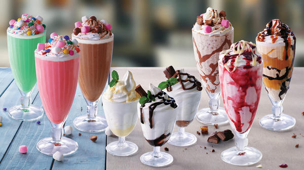 Different sorts of Wimpy shakes lined up on a table.