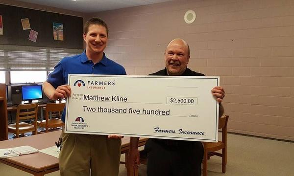 Agent poses with teacher recipient of donation.
