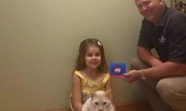 Bob hands a DQ gift card to a small girl who is smiling at the camera