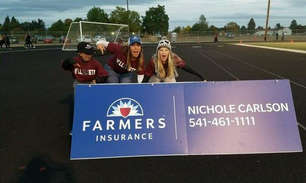 Middle school children use a sign to cheer for their favorite team: Farmers Insurance!