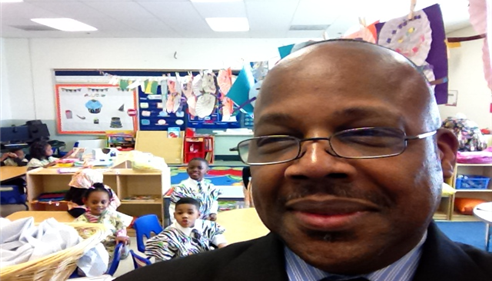 Man taking a selfie while visiting kids at a school