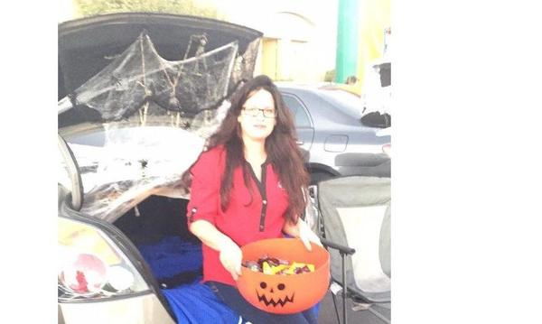 woman holding jack o lantern bucket with treats.