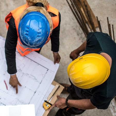 Aerial view of two people in hard hats reviewing a blueprint