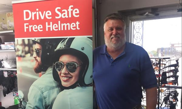 "Stephen is smiling with a sign that reads ""Drive Safe Free Helmet"""