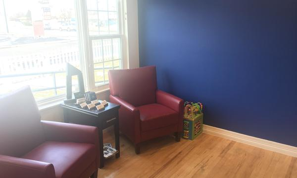 two maroon chairs by a blue wall.
