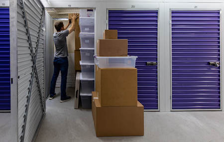 Man stacking boxes in his storage unit