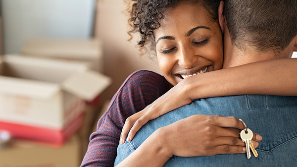 A woman smiles as she hugs her partner while holding the keys to their new home.