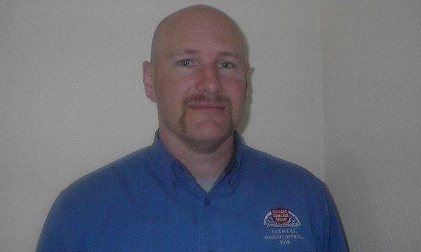 A photo of Agent Michael Gurney, wearing a blue Farmers Insurance shirt.