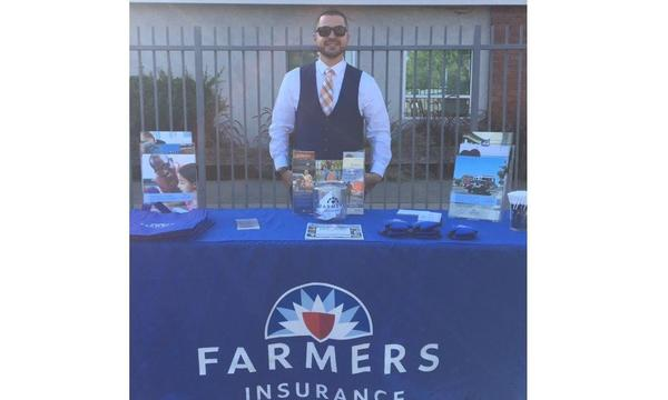 Agent Jaime Diaz standing with his Farmers Insurance promotional table, outside at a school event.