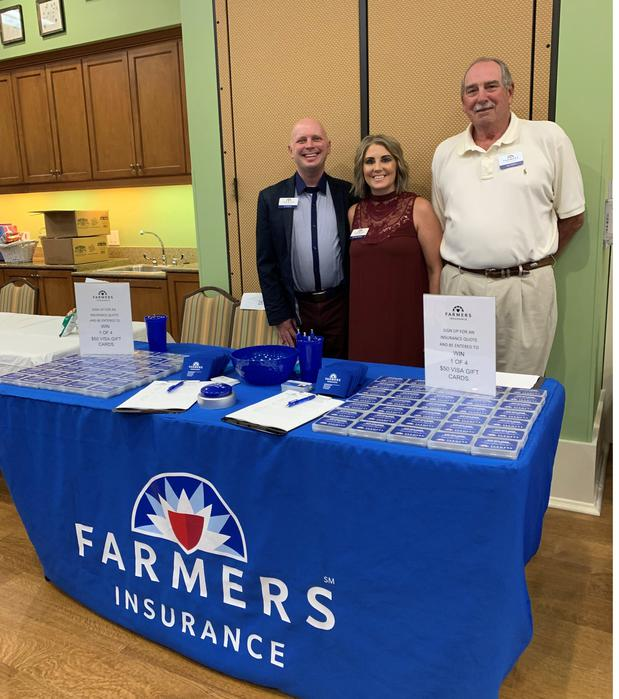 Three people smiling behind Farmers Insurance booth