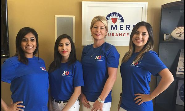 Four women wearing Farmers Insurance shirts standing in front of a Farmers Insurance logo on the wall behind them.