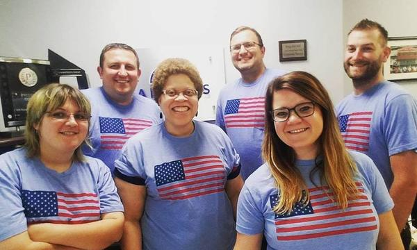 Six people posing for a photo, wearing American Flag shirts.
