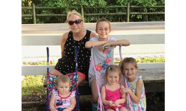 Female staff member with her 4 granddaughters. two of them in a stroller.