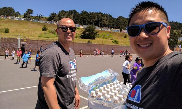 Two men standing with bottles of water on a playground