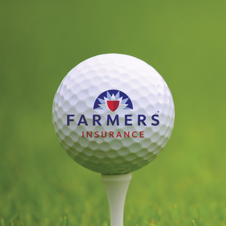Photo of a golf ball on a tee, with the Farmers Insurance logo on the ball.
